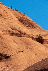 Navajo family climb slickrock into Canyon de Chelly