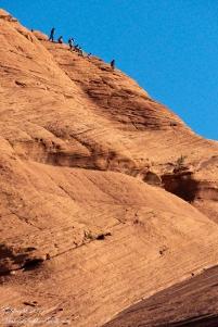Navajo family climb slickrock into Canyon de Chelly