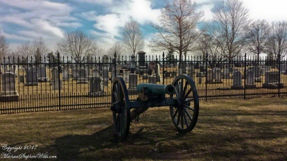 Looking through the iron fence toward the neighborind Evergreen Cemetery, a Union cannon in the foreground.