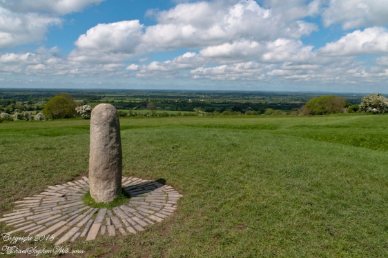 """View northwest from Hill of Tara looking across County Meath with views of Counties Westmeath and Cavan. On the horizon, right, is Hag's Mountain, (Irish: Sliabh na Caillí) , site of the Loughcrew Cairns. The standing stone is the """"Stone of Destiny: (Irish: Lia Fáil), which served in coronation the coronation of the High Kings of Ireland. It stands on the Inauguration Mound (Irish: an Forrad) of Tara. This photograph was taken the morning of May 27, 2014 hours before the stone was vandalized, doused with green and red paint."""