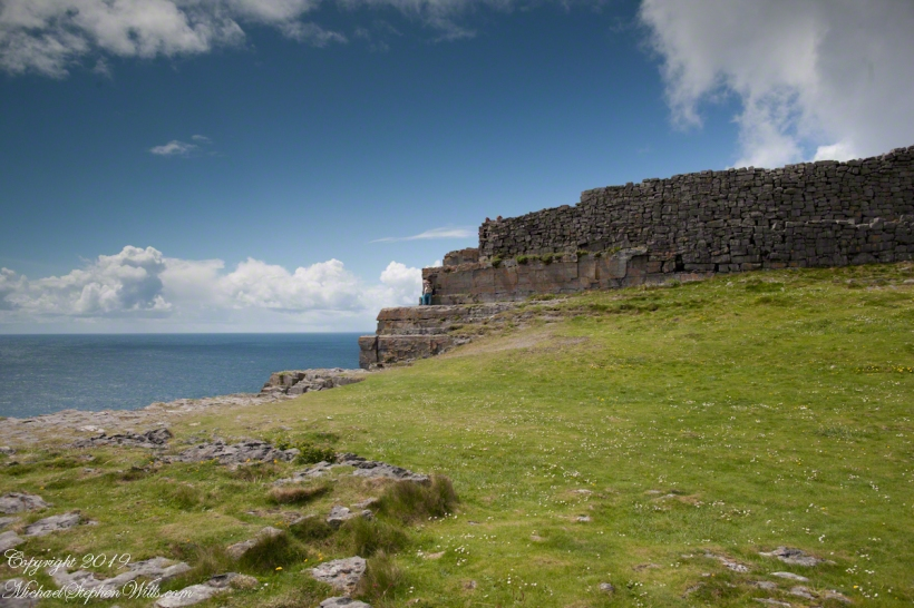 Ancient fort wall with tourists and Cliff Edge of Dun Aonghasa (Dun Aengus)